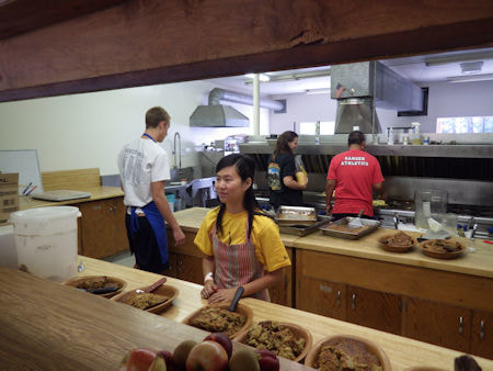 Photo looking into the kitchen with staff working.